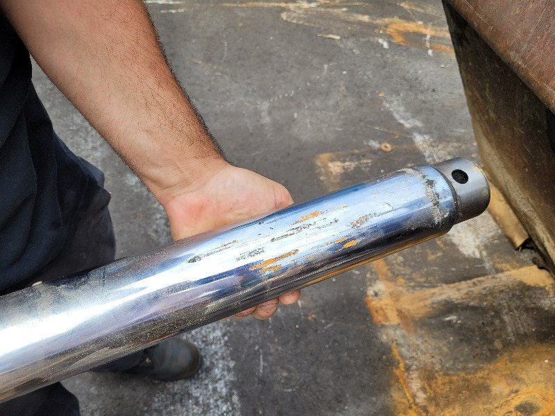 Example of a bad hydraulic rod. The damage on the rod causes lost of pressure and fluid leaks making the forklift unsafe to use.